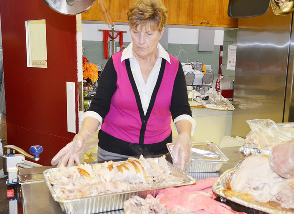 WARREN DILLAWAY / Star Beacon<br /> BRENDA LEERS, a volunteer at Lighthouse Harvest Foundation, prepares Thanksgiving dinner at the old armory building on State Road in Ashtabula Township.