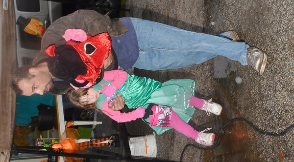 WARREN DILLAWAY / Star Beacon<br /> MATTHEW ENOS lifts Madison Enos, 5, over a water puddle while holding Zoe Nicole Enos, 10 months, during a rainy evening of trunk or treating at the North Kingsville Village Hall.