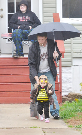 WARREN DILLAWAY / Star Beacon<br /> TOM MCSKIMMING helps his daughter Gabriella after getting candy from Tyler DiBell during trick or treating on West 46th Street in Ashtabula on Saturday afternoon.
