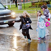 TRICK OR TREATERS jump a water puddle while looking for candy at the Kingsville Fire Department on Saturday evening. (From left) Ava Camplese of Kingsville Township , Serenity Thompson of Ashtabula and Miranda Navarro don't seem too concerned about the rain.