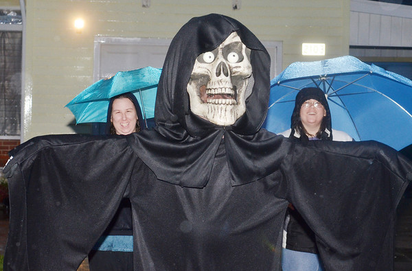 WARREN DILLAWAY / Star Beacon<br /> A SCARY creaure doesn't sseem to bother Kathy (left) and Nikki Green during a rainy Thursday evening o trick or treating in Ashtabula Township.