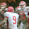 WARREN DILLAWAY / Star Beacon<br /> JARRAD HARRAH of Edgewood (left with ball) celebrates with Warrior teammates Jayson Greenwood (63) annd Connor McLaughlin (9) after Harrah ran an interception back for a touchdown on Saturday at Lutheran East in Cleveland Heights.