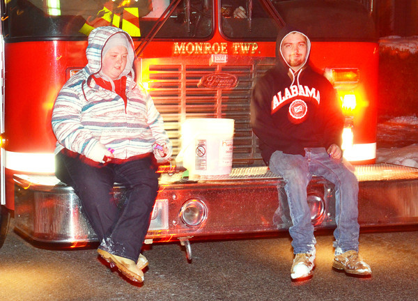 WARREN DILLAWAY / Star Beacon<br /> CANDY TOSSERS ride on the front of a Monroe Township fire truck on Friday evening during the Conneaut Christmas Parade.