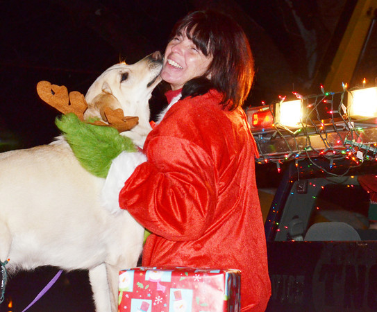 WARREN DILLAWAY / Star Beacon<br /> CHRISSY MCCARTNEY of State Street Auto gets a lick from Sadie, playing the Grinch's dog, on Friday night before the Conneaut Christmas Parade.
