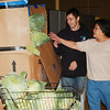 WARREN DILLAWAY / Star Beacon<br /> ANGIE GASCH and Ian Williams prepare to provide lettuce during a regular food giveaway at the Conneaut Human Resources Center.