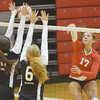 WARREN DILLAWAY / Star Beacon<br /> KIRSTIE OTTO (17) of Geneva spikes the ball as Kelly Lang (far left) and Mary Prosuch (6), both of Eastlake North, reach for the block on Thursday at Geneva.