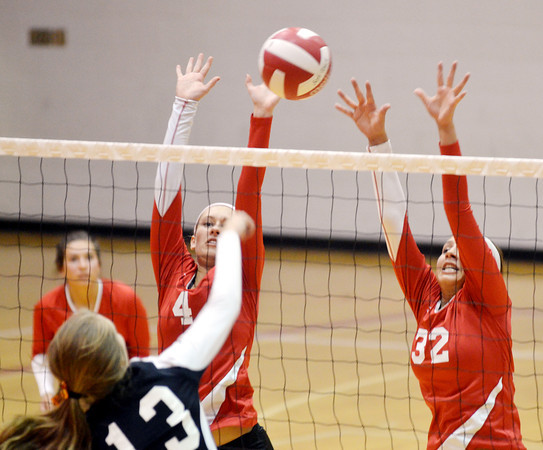 WARREN DILLAWAY / Star Beacon<br /> MEGAN COOL (4) and Geneva teammate Emily Ball leaps       for a block of a spike by Kate Snyder of Eastlake North on Thursday night at Geneva.