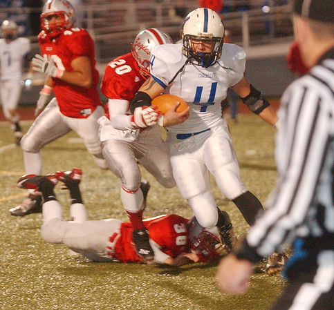 WARREN DILLAWAY / Star Beacon<br /> MARK MURRAY (4) of Madison tries to find running room with Geneva tacklers Austin Clutter (20) and Mike Galloway (38) in hot pursity with Eagle Eric Juncker (40) Thursday night against Madison.