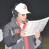 WARREN DILLAWAY / Star Beacon<br /> JOSH FRANKE, Edgewood football coach, checks out plays during a home game with Gilmour Academy on Friday night.