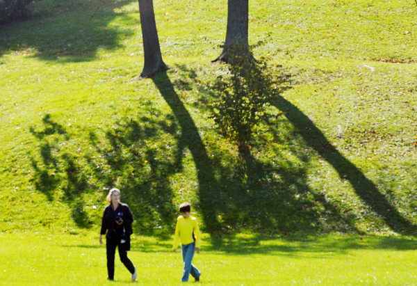 WARREN DILLAWAY / Star Beacon<br /> LORI DECOST and her son Gavin Franks, 8, both of Bazetta walk in front of reflected trees on Friday at Lake Shore Park in Ashtabula Township.