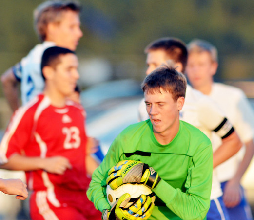 WARREN DILLAWAY / Star Beacon<br /> JACK REGER, Madison goalie, holds the ball tight after making a save on Tuesday evening during a home game with Geneva.