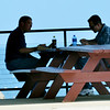 WARREN DILLAWAY / Star Beacon<br /> TWO MEN are silhouetted while eating lunch at Lake Shore Park on Tuesday afternoon in Ashtabula Township.