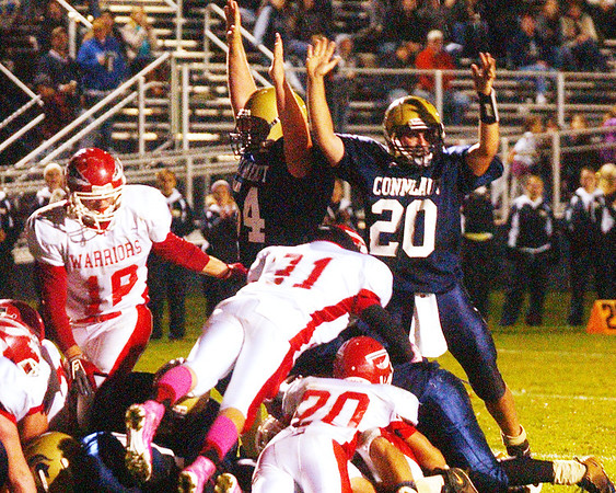 WARREN DILLAWAY / Star Beacon<br /> R.J. NELSON (20) of Conneaut signals a touchdown by Spartan quarterback Troy Colucci Friday night during ahome game with Edgewood. Colucci is beneath a pile of Edgewood defenders.