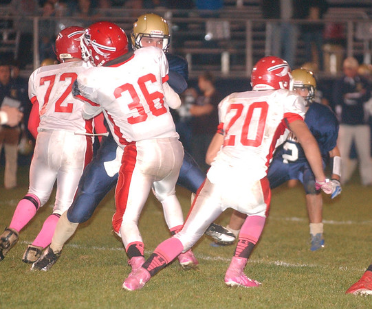 WARREN DILLAWAY / Star Beacon<br /> DYLAN MCCALEB (20) of Edgewood finds a hole behind a block by Warrior teammate Anthony Monda as Tyler Welton (72) looks for someone to block and Conneaut's Brandon Luce (2) closes in Friday night at Conneaut.