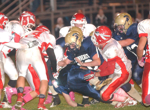 WARREN DILLAWAY / Star Beacon<br /> EDGEWOOD DEFENDER Anthonie Magda (right middle) starts to lose his helmet as Conneaut's Troy Colucci (middle falling) fights for an extra yard Friday night at Conneaut.