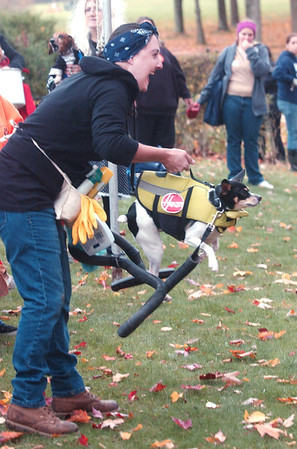 WARREN DILLAWAY / Star Beacon<br /> TERRY RACINSKAS of Geneva lits her dog Barkley after winning the most creative costume contest at the Ashtabula County Animal Protective League Boo Wow Walk at Maple Ridge Golf Course in Saybrook Township Saturday. The swim vest found a new use when Barkley didn't care for swimming.