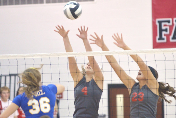 WARREN DILLAWAY / Star Beacon<br /> MEGAN COOL (4) and Sara Juncker (23) of Geneva leap for a block of a spike by Victoria Glunt of Notre Dame Cathedral Latin on Tuesday night during a Division II District semifinal at Jefferson.