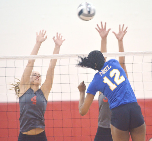 WARREN DILLAWAY / Star Beacon<br /> MEGAN COOL (4) and Emily Ball (face hidden) of Geneva leap for a block of a spike by Ambre Pierce of Notre Dame Cathedral Latin on Tuesday night during a Division II District semifinal at Jefferson.