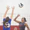 WARREN DILLAWAY / Star Beacon<br /> EMILY BALL (32) of Geneva leaps to spike the ball as Emily Weigand of Notre Dame Cathedral Latin leaps for a block on Tuesday night during a Division II District semifinal at Jefferson.