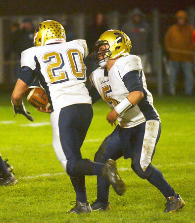 WARREN DILLAWAY / Star Beacon<br /> TROY COLUCCCCI (5), Conneaut quarterback, hands off  to running back R.J. Nelson on Friday night at Edgewood.