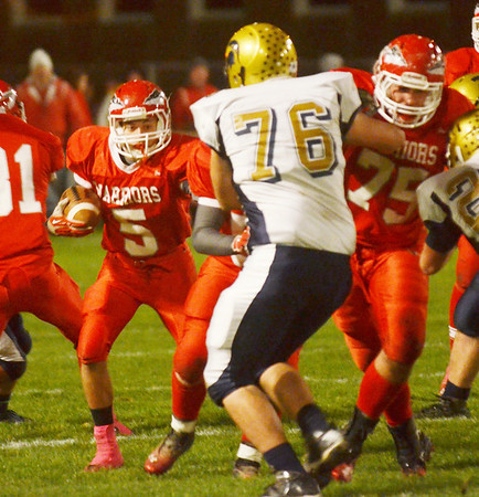 WARREN DILLAWAY / Star Beacon<br /> RIIS SMITH (5) of Edgewood looks for running room while fellow Warrior Matt Fitchet (75) blocks James Brunning of Conneaut on Friday night at Edgewood.