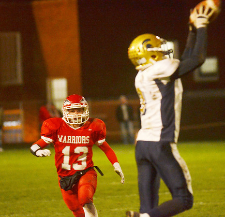 WARREN DILLAWAY / Star Beacon<br /> MASSO LILJA (13) of Edgewood watches as C.J. Rice of Conneaut pulls in a pass on Friday night at Edgewood.