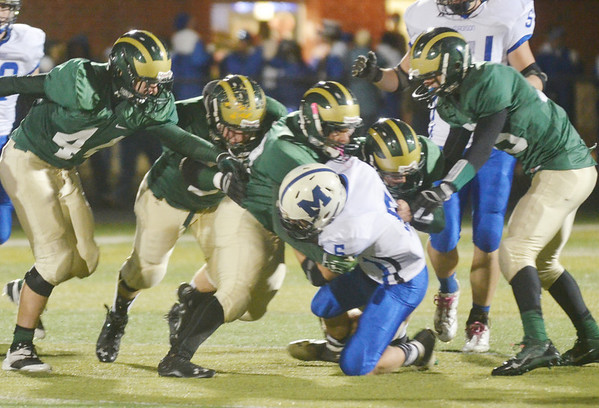 WARREN DILLAWAY / Star Beacon<br /> BRANDON DAVIS of Madison (5) is brought to the ground by a group of Lakeside tacklers on Friday night at Lakeside.