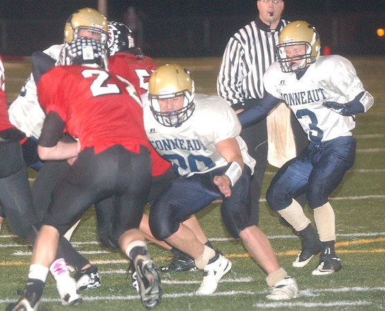 WARREN DILLAWAY / Star Beacon<br /> JUSTIN BUTLER (22) of Jefferson tries to find running room as Conneaut defenders R.J. Nelson (20) and Kyle Prevot (3) Friday night in Orwell.