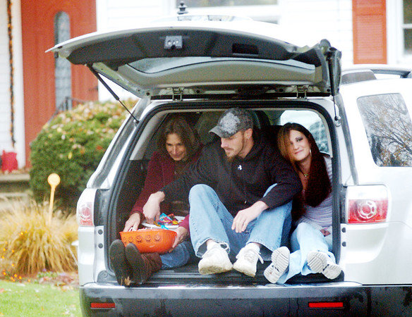 WARREN DILLAWAY / Star Beacon<br /> ANN WILLHOITE (left),  Josh Willhoite and Kendra Johnson try to stay dry while waiting for trick or treaters Saturday afternoon on West Erie Street in Jefferson.