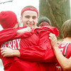 WARREN DILLAWAY / Star Beacon<br /> DEVIN PRITSCHAU (facing with headband) hugs Blaine Luszcak after the Perry Pirates qualified for the Division II state cross country meet next week in Columbus.