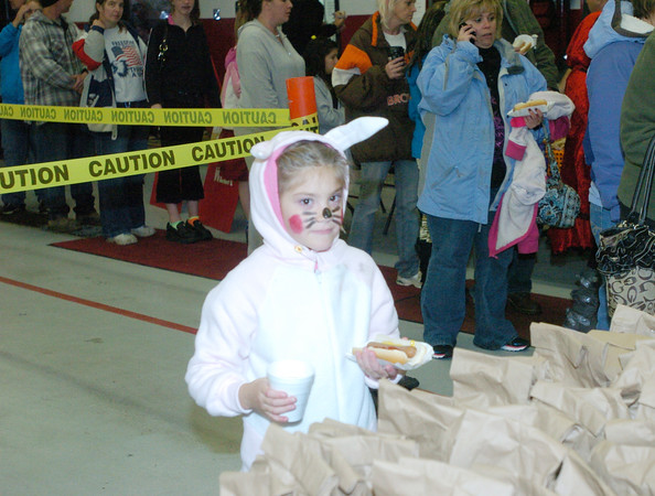 WARREN DILLAWAY / Star Beacon<br /> TEAGAN GILBERT, 7, of Geneva enjoys a hot dog and a drink during Ghoulfest Saturday evening at the Geneva Fire Department.