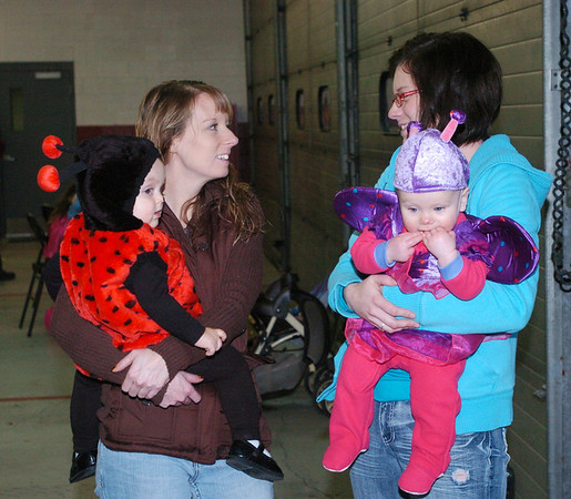 WARREN DILLAWAY / Star Beacon<br /> KRYSTAL PATRICK (right) and her daughter Sophie Odegard, eight months, and Gennie Platz and her daughter Payton Brooks, 18 months, enjoy Ghoulfest fun at the Geneva Fire Department Saturday evening.