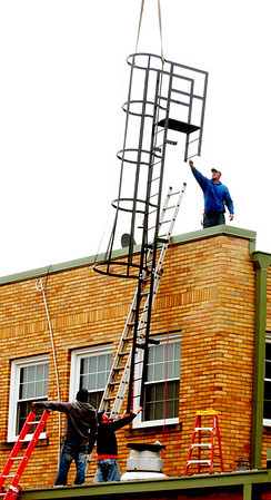 WARREN DILLAWAY / Star Beacon<br /> RYAN ADAMS (top) and fellow Building Technicians employees Matt Peet (lower left) and Mike Meehan put a new roof escape on the Western County Court building Tuesday afternoon.