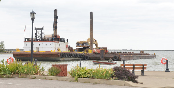 WARREN DILLAWAY / Star Beacon<br /> A SMALL boat is dwarfed by a barge dredging in Conneaut Harbor on Monday.