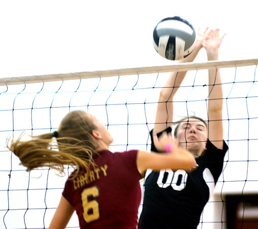 WARREN DILLAWAY / Star Beacon<br /> BAILEY BECKWITH of Jefferson (facing) reaches to spike the ball while Courteney Lukac (6) leaps for the block on Tuesday evening at Jefferson.