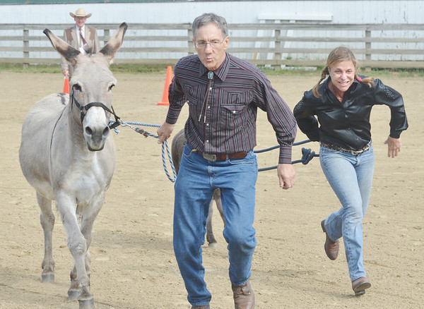 WARREN DILLAWAY / Star Beacon<br /> MEL MILLIRON (left) of Southington and Stacey Kovach of Munson Township participate in donkey races on Saturday at The Great Geauga County Fair.