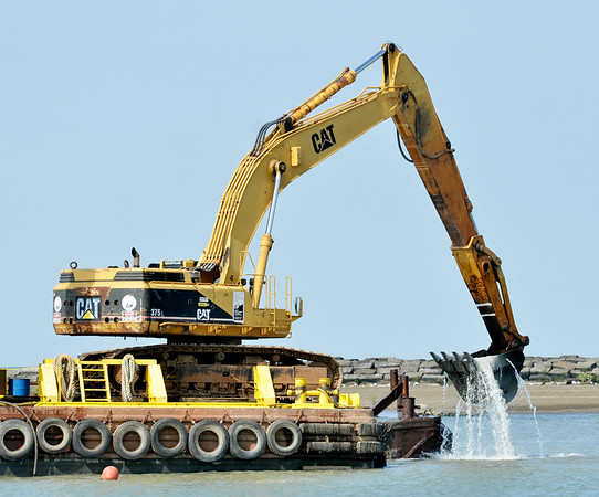 WARREN DILLAWAY / Star Beacon<br /> A LARGE barge is used to dredge the eastern channel of Conneaut Harbor on Monday morning.