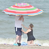 WARREN DILLAWAY / Star Beacon<br /> ANDREA AND Jason Kanyuh of Madison set up an umbrella during a trip to the beach at Geneva State Park on Monday.