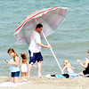 WARREN DILLAWAY / Star Beacon<br /> JASON KANYUH of Madison sets up an umbrella during a trip to the beach at Geneva State Park on Monday.