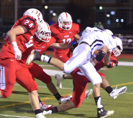 WARREN DILLAWAY / Star Beacon<br /> BRANDON DAVIS, a Madison running back, gets dragged down by a host of Perry tacklers including Kyle Beyer (24) and Shane Raddatz (12).