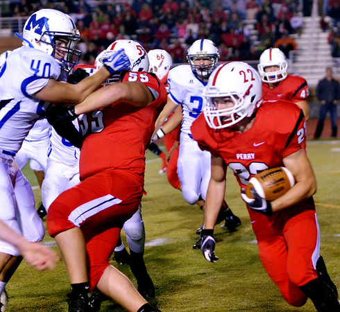 WARREN DILLAWAY / Star Beacon<br /> ZAKARY HURD (22) of Perry looks for running room on Friday night at teammate Connor Lowe (55) blocks Jack Holl of Madison on Friday night at Perry.
