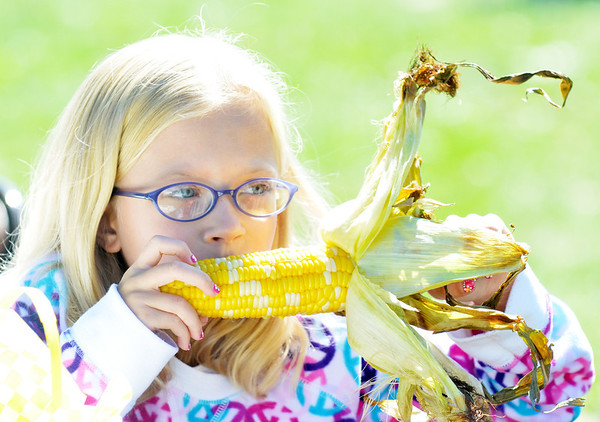 WARREN DILLAWAY / Star Beacon<br /> LEXI WESTERBURG, 8 of Kingsville Township, enjoys corn on the cob at the Conneaut Rib Burn Off on Saturday at Conneaut Township Park.