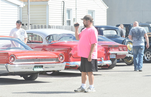 WARREN DILLAWAY / Star Beacon<br /> HOT ROD cars from the 1950s were out in force Saturday along the Strip at Geneva-on-the-Lake during the first edition of the American Graffitti North Shore. Dave Davis (center) of Geneva-on-the-Lake takes pictures of the event.