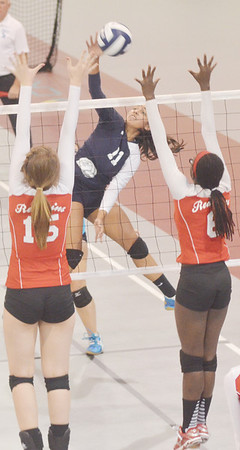 WARREN DILLAWAY / Star Beacon<br /> ALICIA NGIRAINGAS (11)  of St. John spikes the ball as Jessica Fontana (15) and Ledgemont teammate Rachel Formica leap for a block on Monday at Spire Institute in Harpersfield Township.