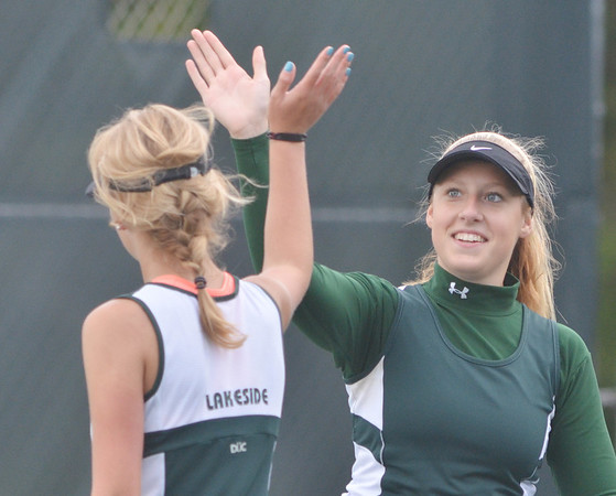 WARREN DILLAWAY / Star Beacon<br /> COURTNEY SMITH (facing) high fives with Lakeside first doubles partner Ashley Gran on Monday during a match with Geneva.