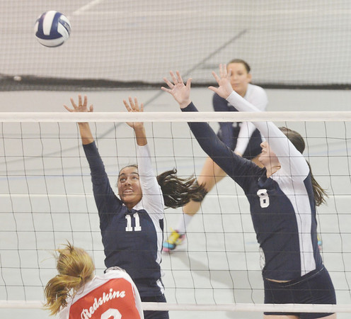 WARREN DILLAWAY / Star Beacon<br /> MACKENZIE STENROOS (8) of St. John and Herald teammate Alica Ngiraingas (11) leap for a block of a spike by Cassandra Ohler of Ledgemont  on Monday at Spire Institute in Harpersfield Township.