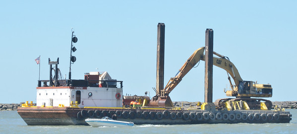 WARREN DILLAWAY / Star Beacon<br /> A SMALL boat is dwarfed by a barge dredging in Conneaut Harbor on Tuesday.