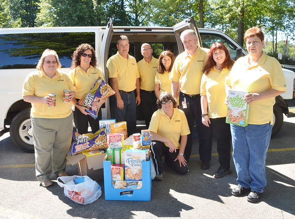 WARREN DILLAWAY / Star Beacon<br /> CHROMAFLO TECHNOLOGIES employees display food gathered for the Lighthouse Harvest Foundation Backpack program. (From left) Judy Parker, accountant; candy McCoy, sales administrative associate; Rich Palmer, production supervisor; Nick Colby, technical service; Jackie Shillling, quality system specialist; Dave Mourissette, plant manager; Jennifer Spink, local area network administrator and Cheryl Young, quality center technician. Karen Sandella, production scheduler, is kneeling.