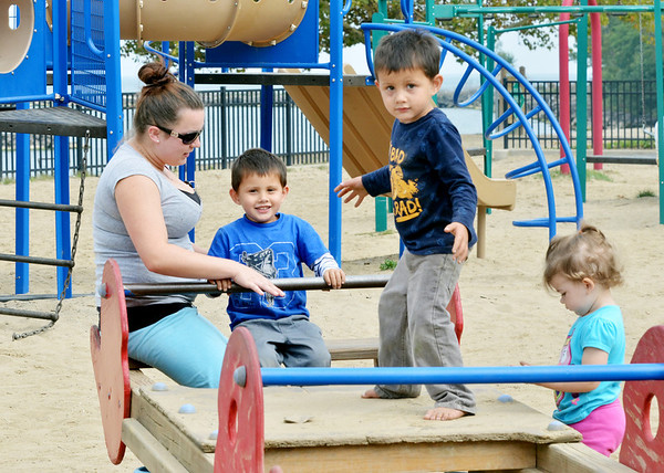 WARREN DILLAWAY / Star Beacon<br /> AKAI PHILLIPS (standing middle) balances on a playground ride as hs mother Amber Goudge and brother Akoni Phillips move the ride and Chloe Reffert (Goudge's niece) hangs out nearby on Thursday at Lake Shore Park in Ashtabula Township.
