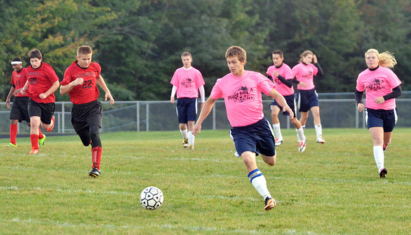 WARREN DILLAWAY / Star Beacon<br /> ZACH UTZ (center), of the co-ed Grand Valley soccer team, races to the ball during a game with Bloomfield on Monday evening.